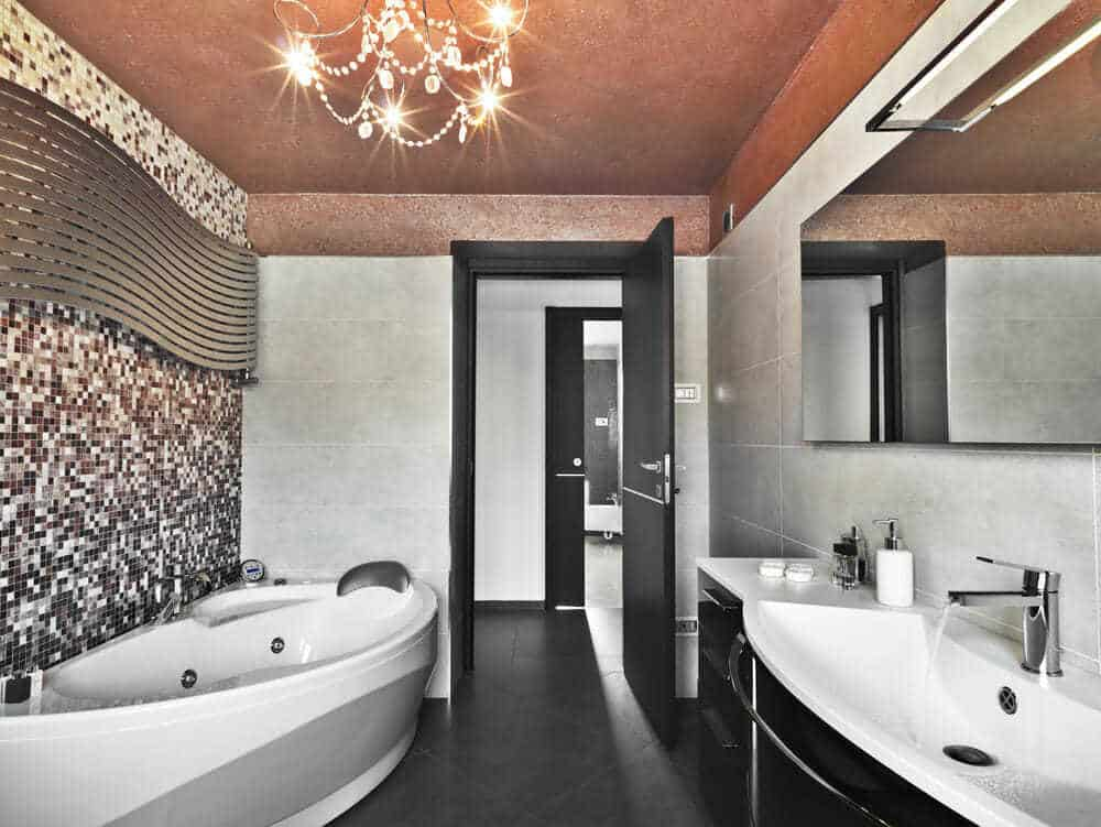 Mosaic style red and black combo on wall is a new trend. Notice the modern curves in the bathtub and sinks.