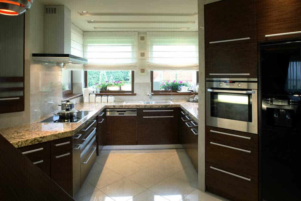 This unusually shaped kitchen uses the large window to bring natural light into the room, which then bounces off the stunning work surfaces and allows the gorgeous dark surfaces to look great without sacrificing the style or size of the kitchen.