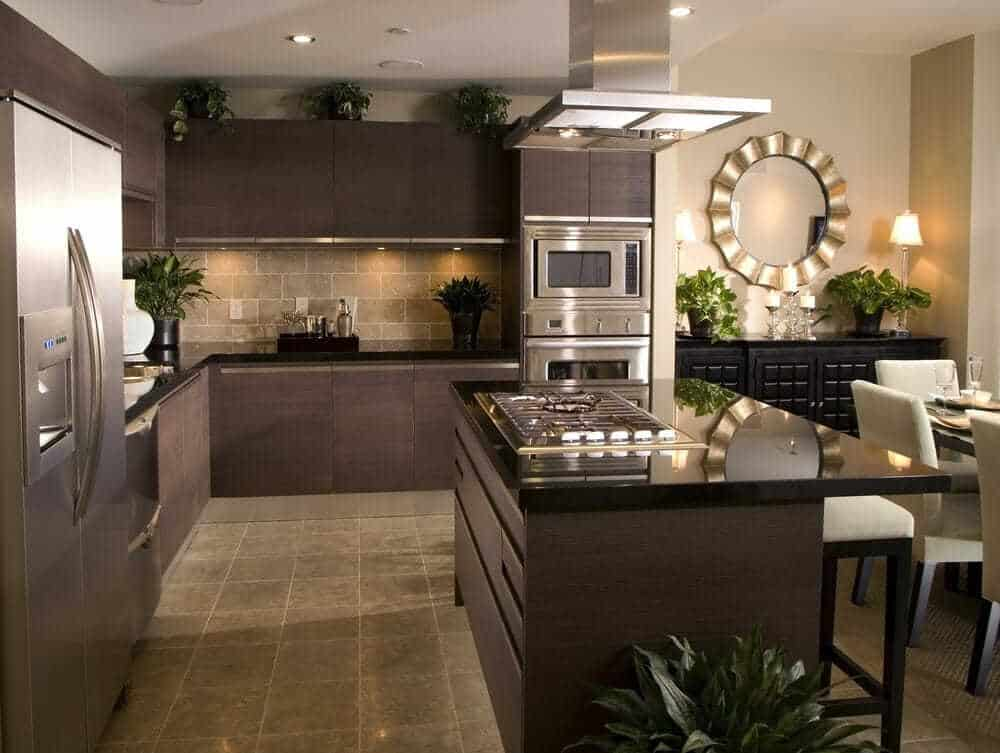 Slate grey kitchen cabinets bring a very stylish and dark edge to the kitchen. This kitchen uses mirrors and semi-matte surfaces to subtly reflect the natural and artificial light.