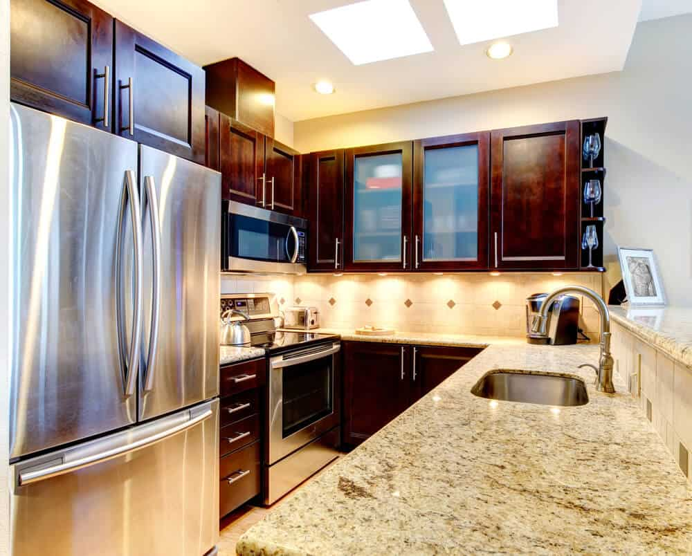 Under cabinet lighting and a very reflective and large refrigerator is a very clever design trick to prevent these gorgeous dark cabinets from absorbing too much light in a small kitchen.