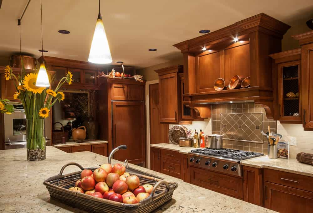 This wholesome family kitchen is comforting, using warm colored cabinets and lots of light and decoration to create a full atmosphere that is enveloping and warming.