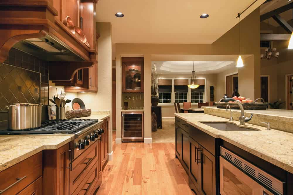 This homely kitchen uses two different styles and colors of dark wooden cabinets. One is warming and homely, while the other adds a more modern and minimal twist to the kitchen.