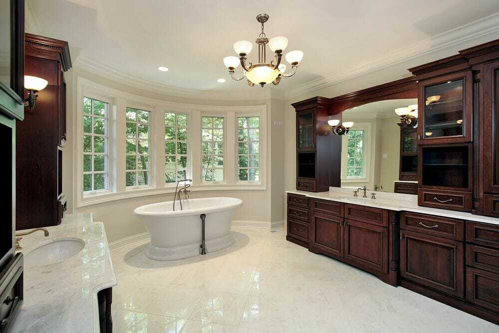 Bay windows surrounding a stand alone tub give s a nice touch along with the custom dark cabinets.