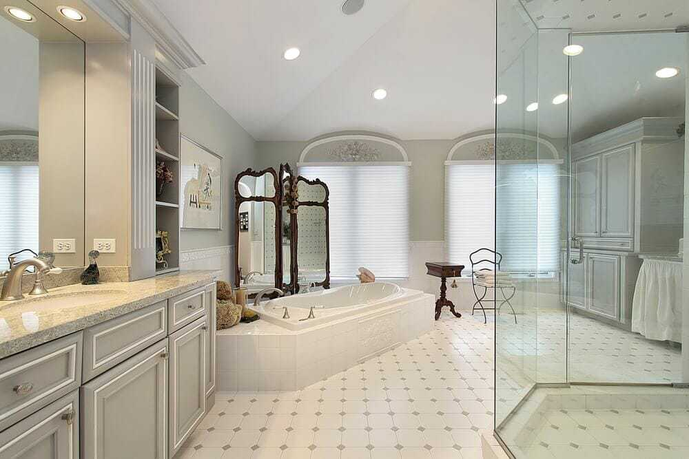 A very spacious room with grey cabinets, granite counters and a stand alone mirror for decor.
