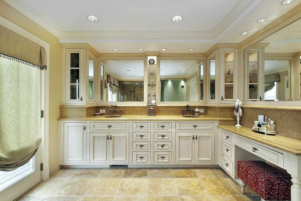"""An """"L"""" shaped room with cabinets that extend along the walls. There are lot s of extra room for storage that is a huge plus for any bathroom."""