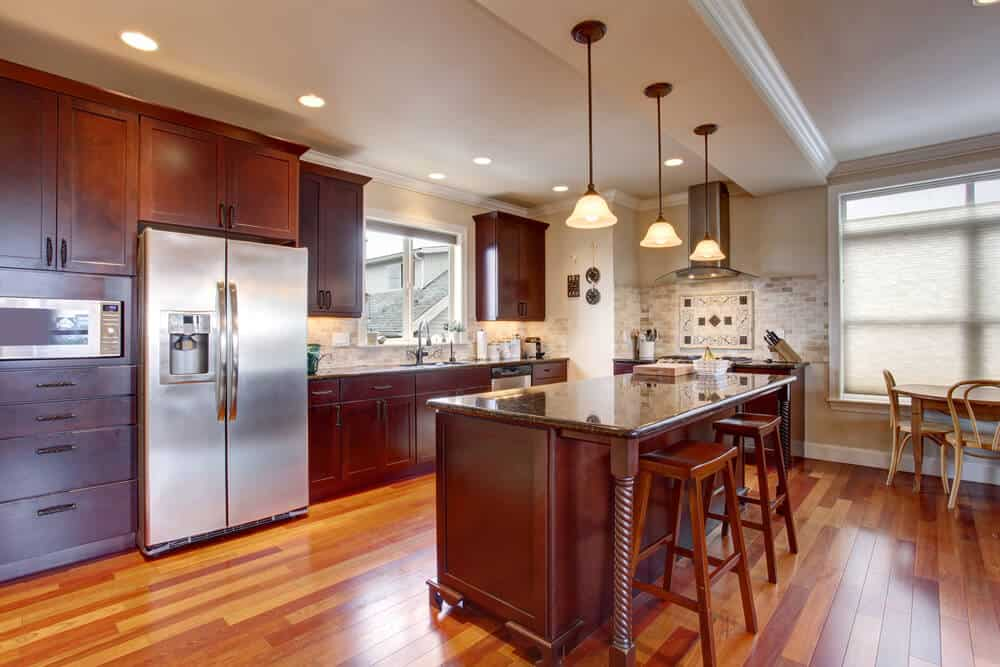 The reflectiveness of these dark kitchen cabinets mean that the mood and style of the kitchen is dictated by the amount of light, natural and artificial, brought into the kitchen. More light will lighten the entire room, but less light will increase the drama and intensity of the dark colors.