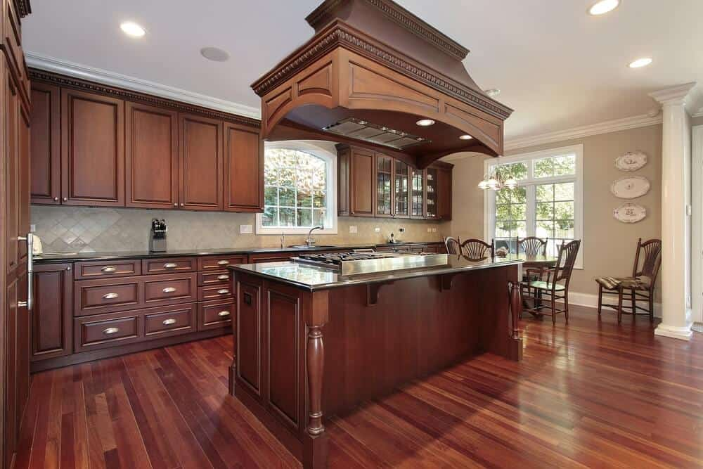 The sheer size of this stand out kitchen island employs the same color as the rest of the stunning cabinet, but its presence in the center of the room and impact multiplies the impact of the gorgeous warm and dark wood used to decorate the entire kitchen.