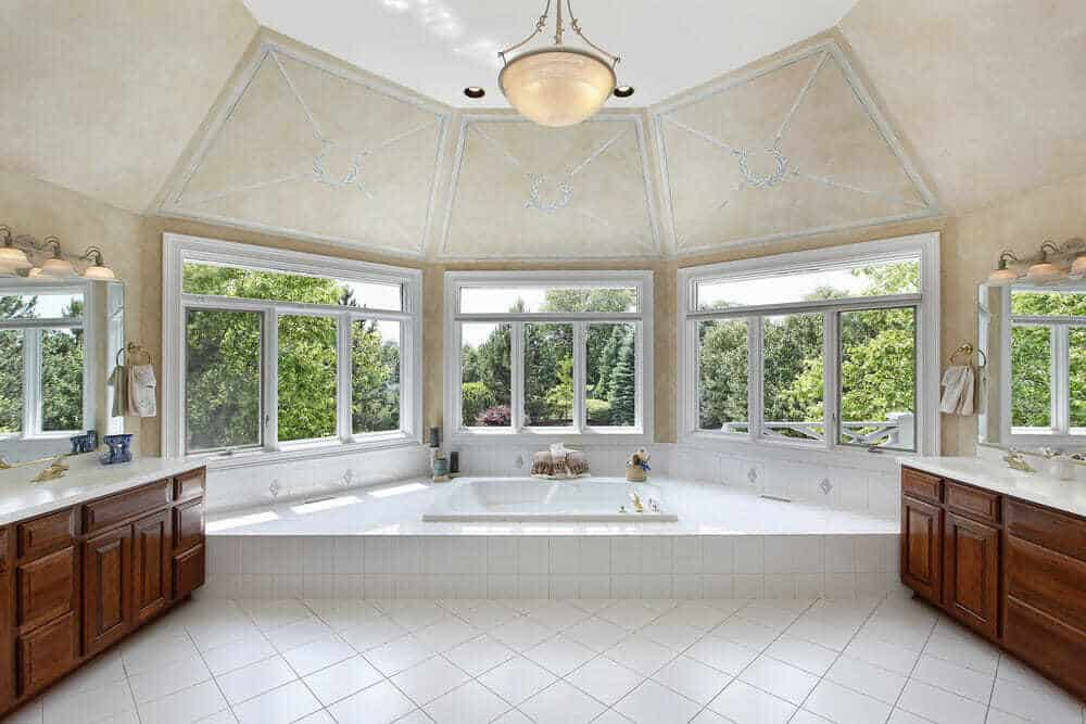 This traditional styled bathroom has two cabinets for storage and the tub as the center piece.