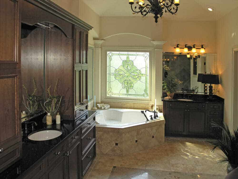 These custom bathrooms are designed with beautiful light tile with dark wooden cabinets that create a wonderful sense of contrast.