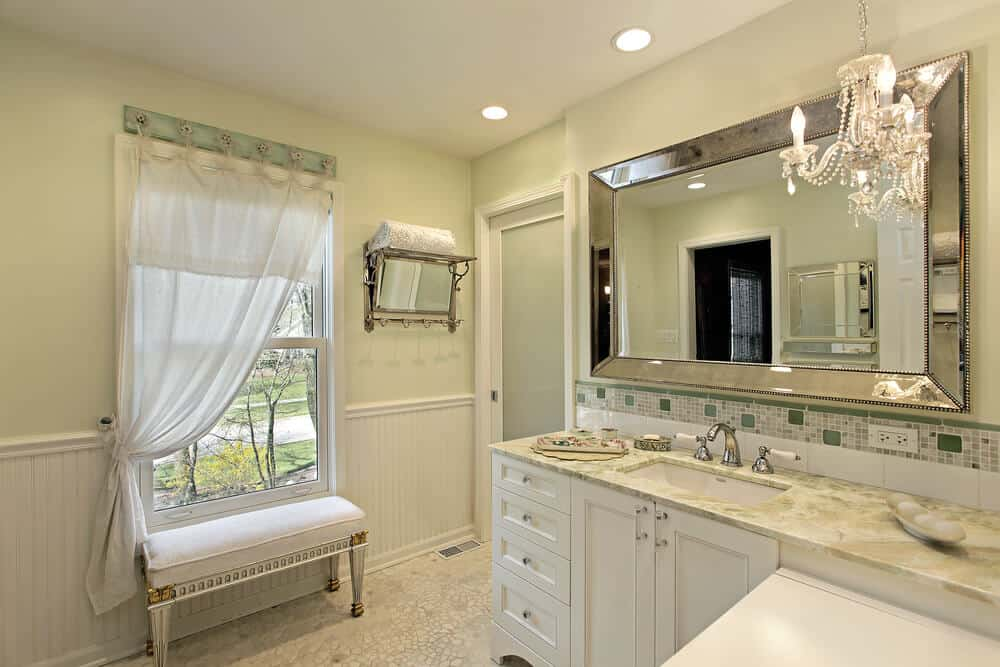 Light colors give a serene yet luxurious feeling to this bathroom. We love the subtle chandelier and silver framed mirror.