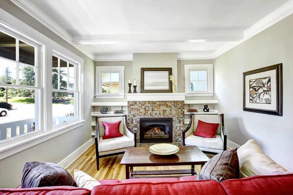 Cozy small living room with fireplace. Room decorated with brown and red pillows