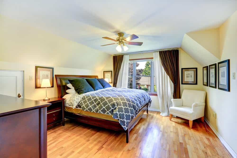 Master bedroom interior with beautiful queen size bed and white armchair in the corner