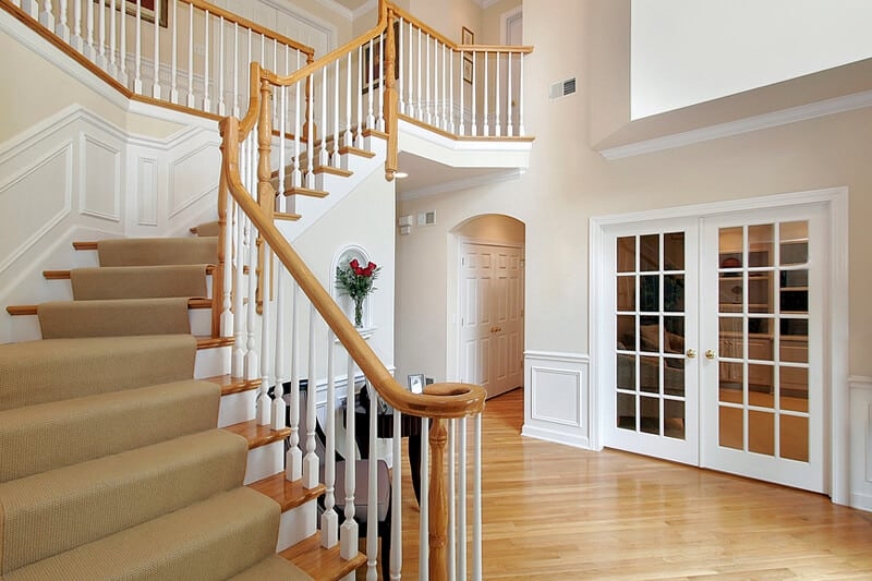 Foyer in luxury home with wood staircase