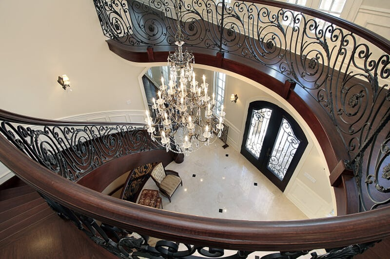 Curved stairway leading down into foyer in luxury home