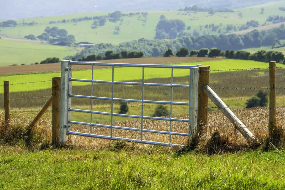 A large aluminum farm gate large enough for large vehicles or animals to pass through.