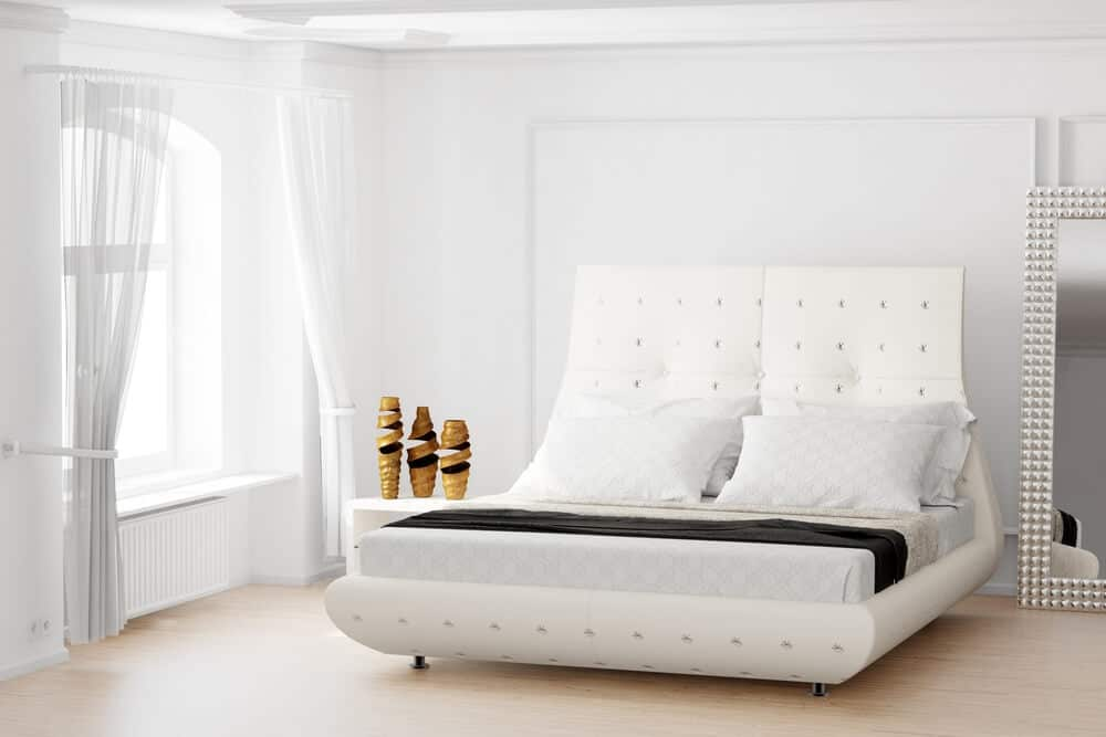 This white bedroom uses textures and headboards with a few accent pieces to create a sense of tranquility.
