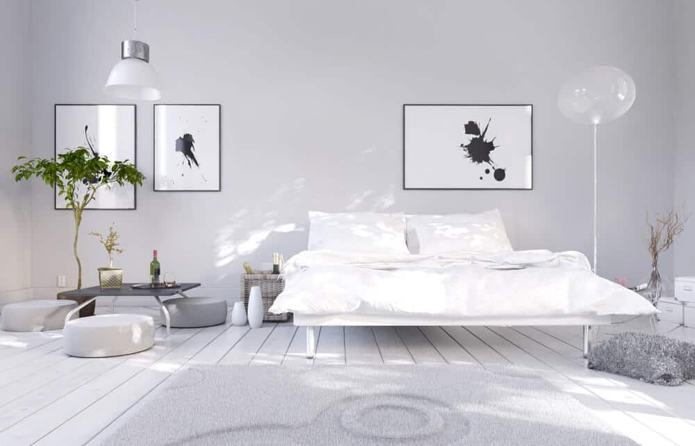 This classy all-white modern bedroom adds a plant and some ink blot prints for a jolt of energy.