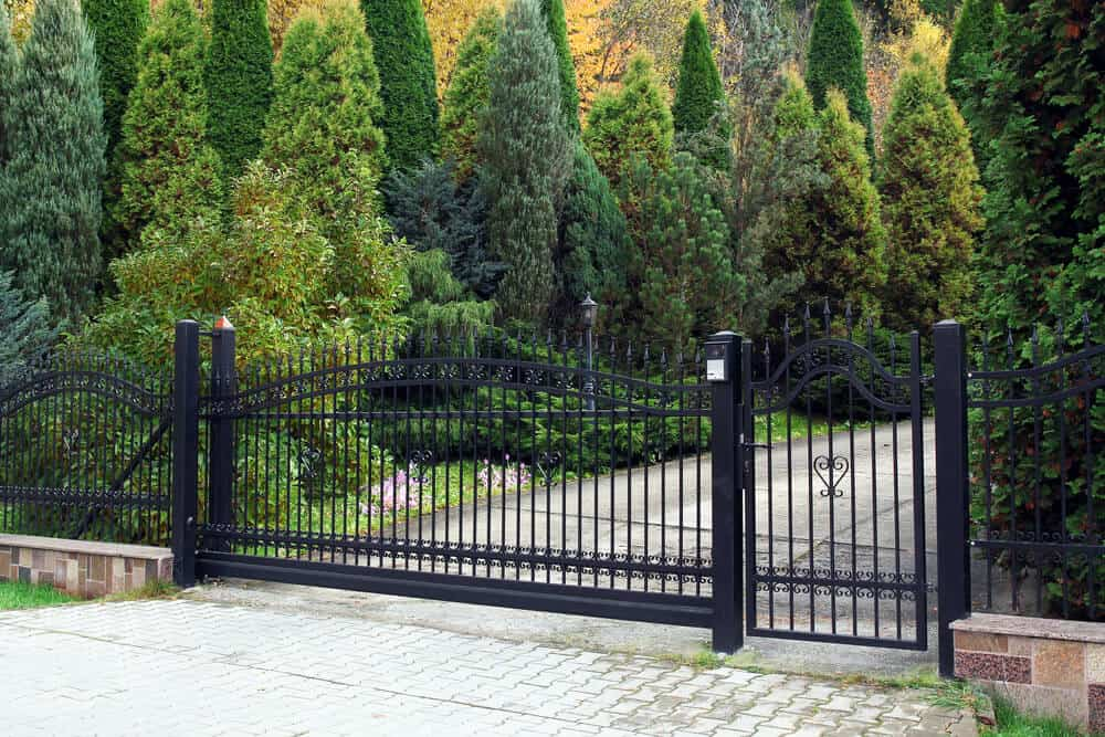This wrought iron gate adds an sophisticated entry point for an car or pedestrian.