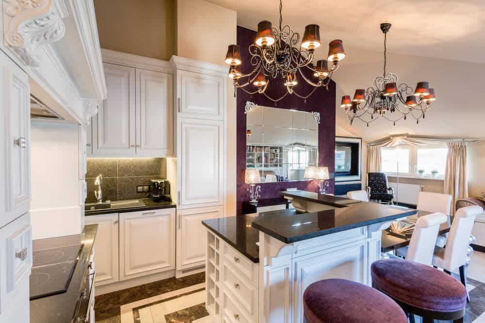 These chandeliers add a touch of elegance to a kitchen when paired with a purple accent wall and velvet bar stools.