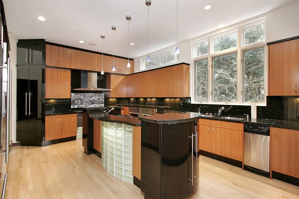 When you pair the black of the countertops with the black accents on the walls and around the cupboards you make the darker honey cabinets really pop out on their own. This kitchen has a unique style all its own.