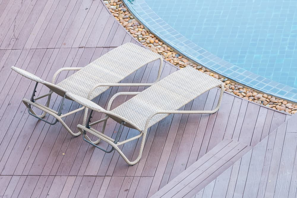 This pool features a light colored wooden deck but also has an added feature, a row of pebbles immediately inside the deck. These pebbles help to filter out any debris that might get into the pool while allowing the water to flow right back through to make a fun but useful accent.