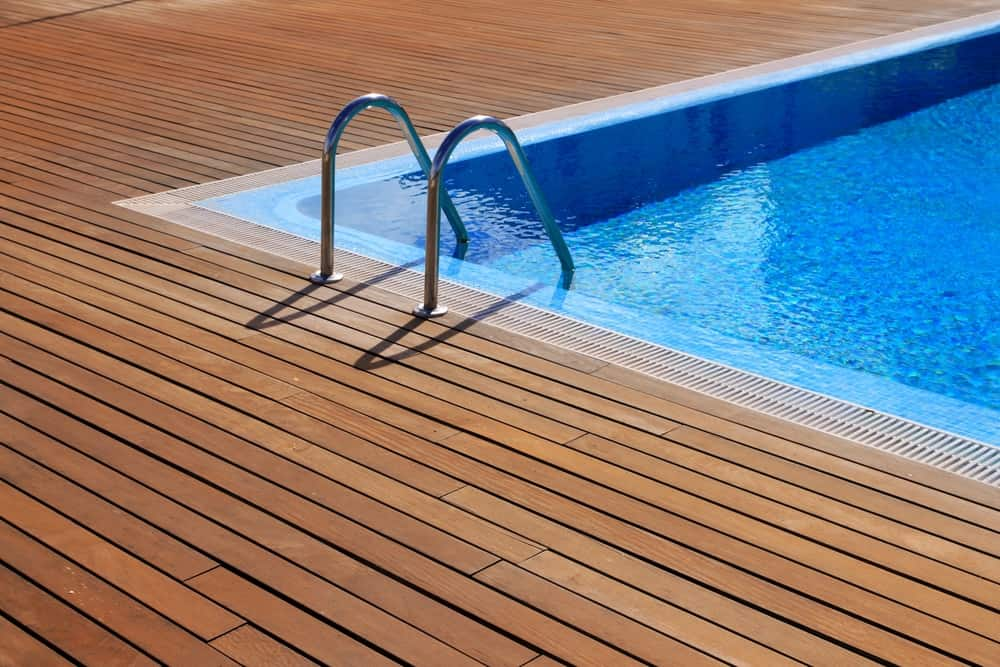These wooden boards are definitely a good quality pool decking and they're going to look great too. The darker color of the wood makes the bright blue really stand out and the wood itself is going to keep you safer getting in and out of the pool.