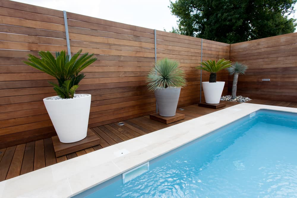 With this deep pool decking you get a stark contrast, but this 'decking' also extends upward to provide a whole lot more privacy for your pool. With the metal bracers and accents, it's definitely a great look that almost feels like a secluded forest.