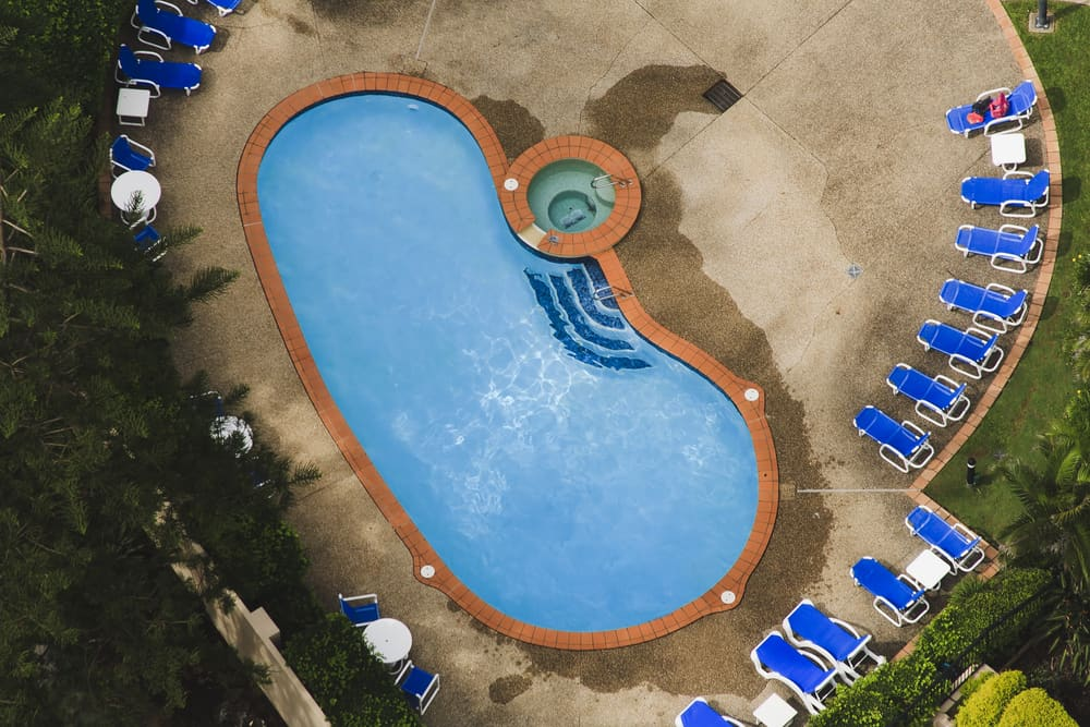 This kidney shaped pool actually has a smaller hot tub built right into the side. That definitely is going to make for a unique shape and it's going to be a lot of fun to swim in.