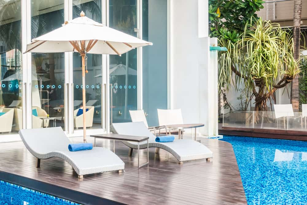 Here's a way to get a deck that's sort of outside the pool and sort of inside it. You've got a small deck with chairs and umbrellas that has a three-sided pool surround.