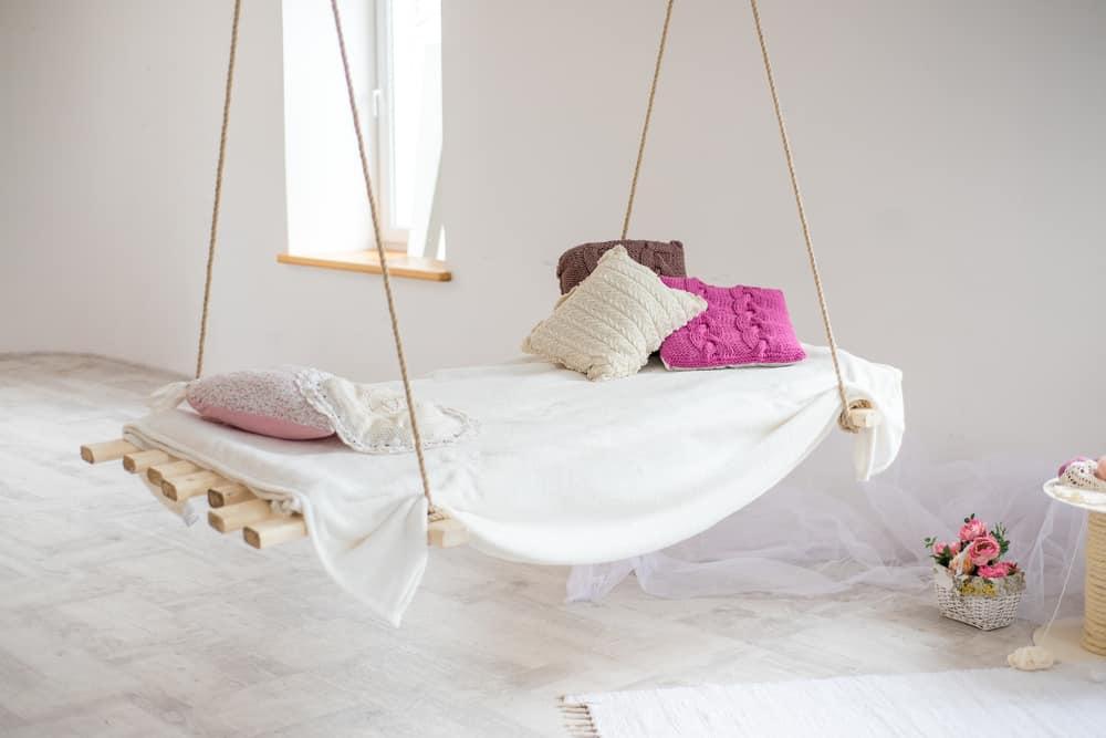 a hanging bed on wood slats